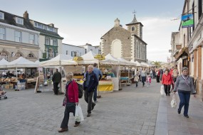 """Keswick, UK - October 15, 2011: Keswick Market. Popular Lake District town, Keswick on Saturday. Several shoppers can be seen walking around serveral market stalls. The Sun was starting to set when this shot was taken. All the stalls are local traders from around the lake district area. Moot Hall Town Hall can be seen in the middle background of the shot."""