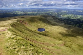 A view looking towards a Tarn (small mountain lake) from Corn du, within the Brecon Beacons National Park in South Wales. There is a large amount of clouds with a blue sky background. The scenery is mountainous and very undulating.